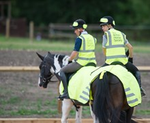 Two BHS Ride Safe riders wearing hi-viz riding on horses