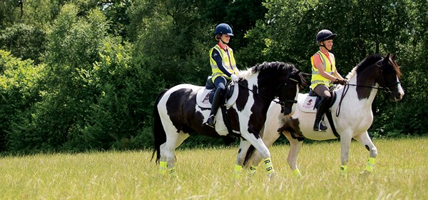 Phoebe Peters and Lizzie Greenwood-Hughes wearing hi-viz riding through field